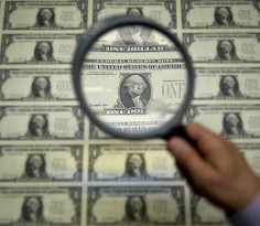 A magnifying glass is held over a 50 subject one dollar note sheet after being printed by an intaglio printing press in this arranged photograph at the U.S. Bureau of Engraving and Printing in Washington, D.C., U.S., on Tuesday, April 14, 2015. Republican efforts to pass a fiscal year 2016 budget cleared another hurdle as the House named its members to a conference committee and Senate Majority Leader Mitch McConnell pledged to do the same by the end of the week. Photographer: Andrew Harrer/Bloomberg