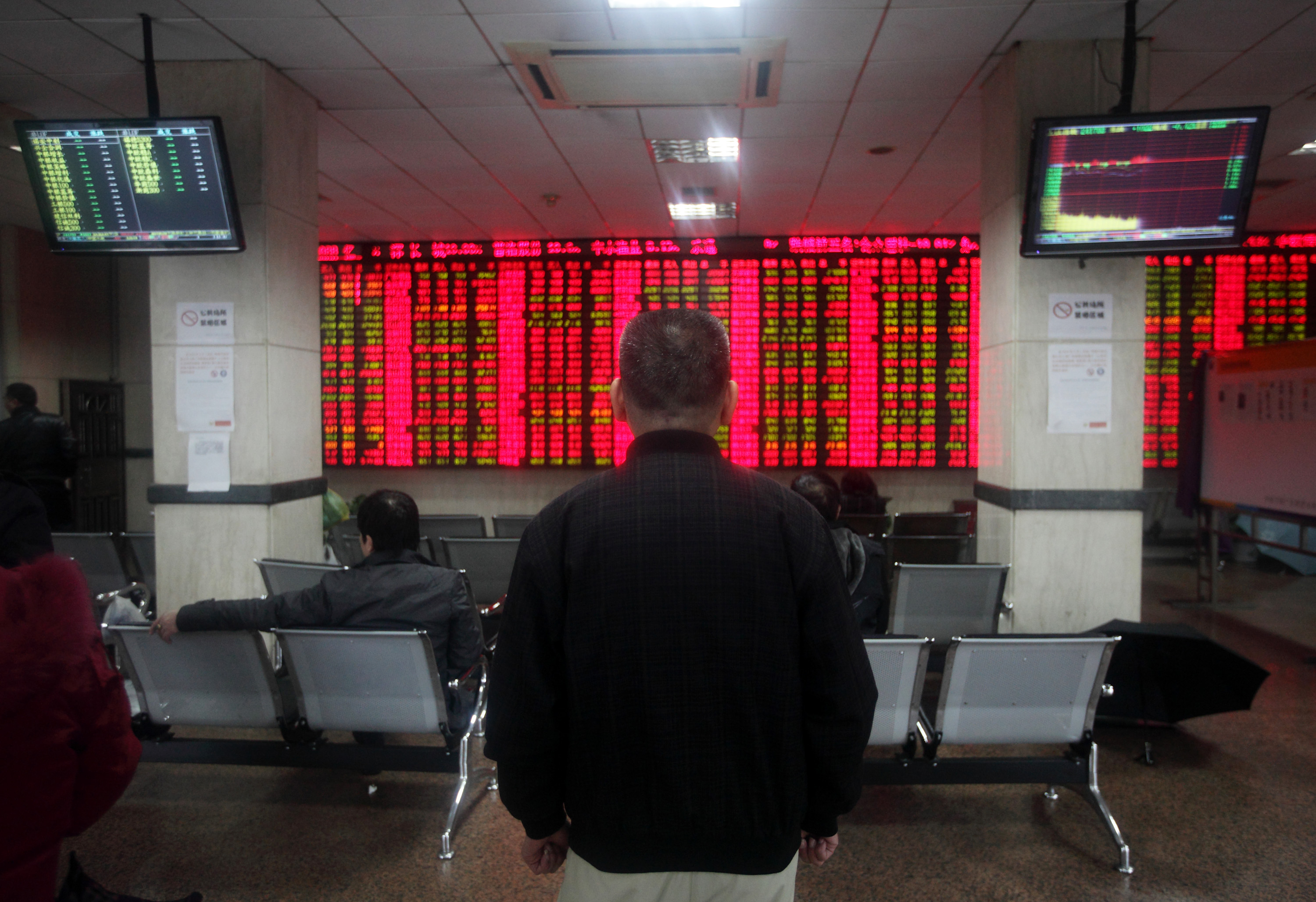 Customers watch share prices on an electronics stock board at a security firm in Shanghai, China, on Tuesday, Feb. 5, 2013. Photographer: Tomohiro Ohsumi/Bloomberg