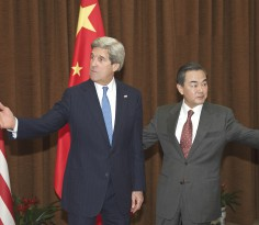 US Secretary of State John Kerry and Chinese Foreign Minister Wang Yi (R) gestures in Beijing on April 13, 2013, to attending meetings with officials.  Kerry arrived in Beijing to seek China's help to rein in a belligerent North Korea and provide a foundation for Seoul to lower soaring tensions with Pyongyang.        AFP PHOTO / POOL / Paul J. Richards
