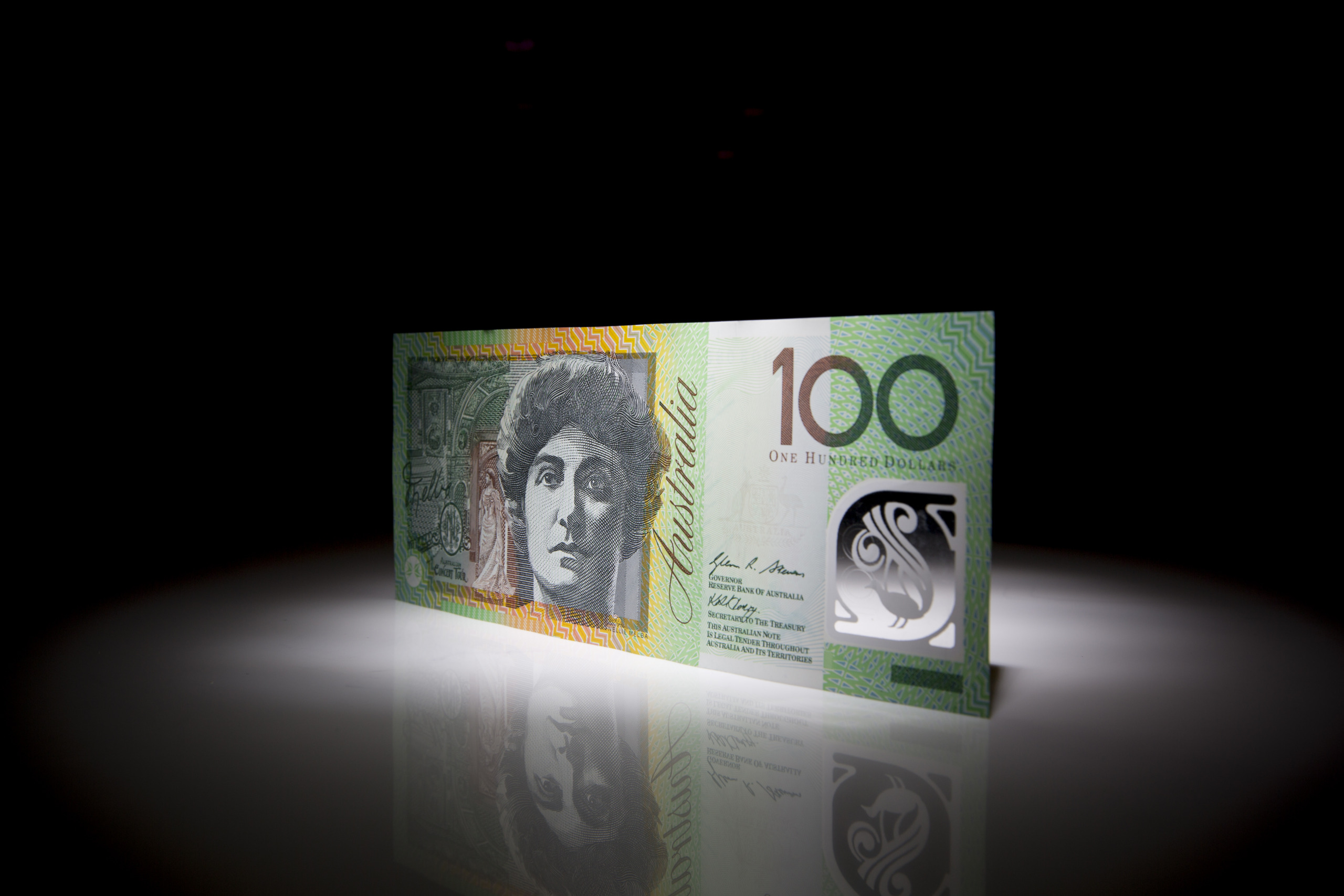 An Australian one-hundred dollar banknote is arranged for a photograph in Hong Kong, China, on Thursday, March 13, 2014. The Australian dollar gained against all of its 16 major peers after data showed employers added more than three times the jobs economists estimated, while New Zealand's dollar jumped to a record on a trade-weighted basis after Reserve Bank Governor Graeme Wheeler became the first head of a major developed central bank to raise interest rates since 2011. Photographer: Brent Lewin/Bloomberg