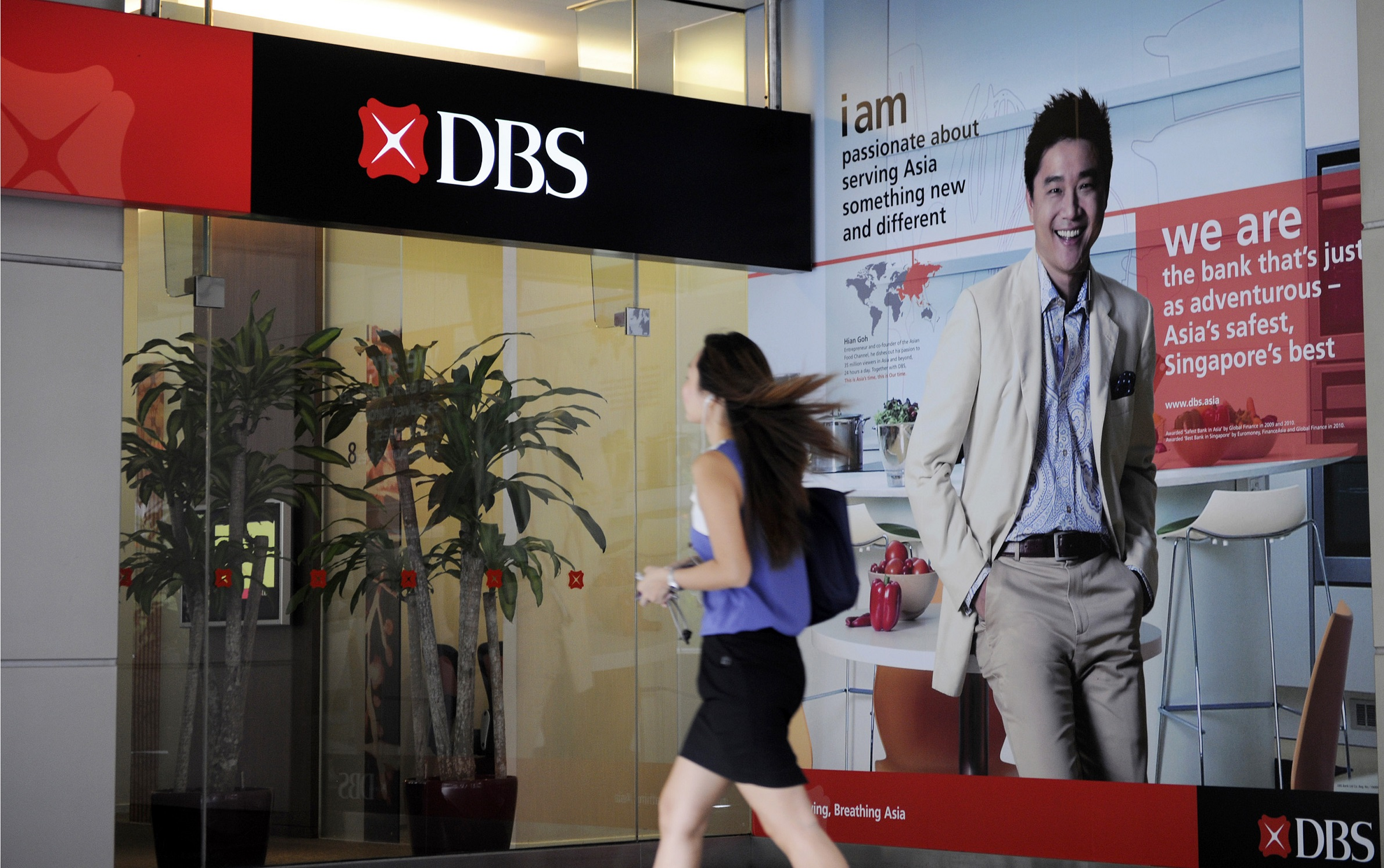 A woman walks past a DBS Group Holdings Ltd. bank branch in Singapore, on Thursday, July 28, 2011. DBS Group Holdings Ltd., Southeast Asia's largest bank, posted second-quarter earnings that missed analysts' estimates as trading income fell 47 percent and loan profitability shrank.  during a results briefing in Singapore, on Thursday, July 28, 2011. Photographer: Munshi Ahmed/Bloomberg