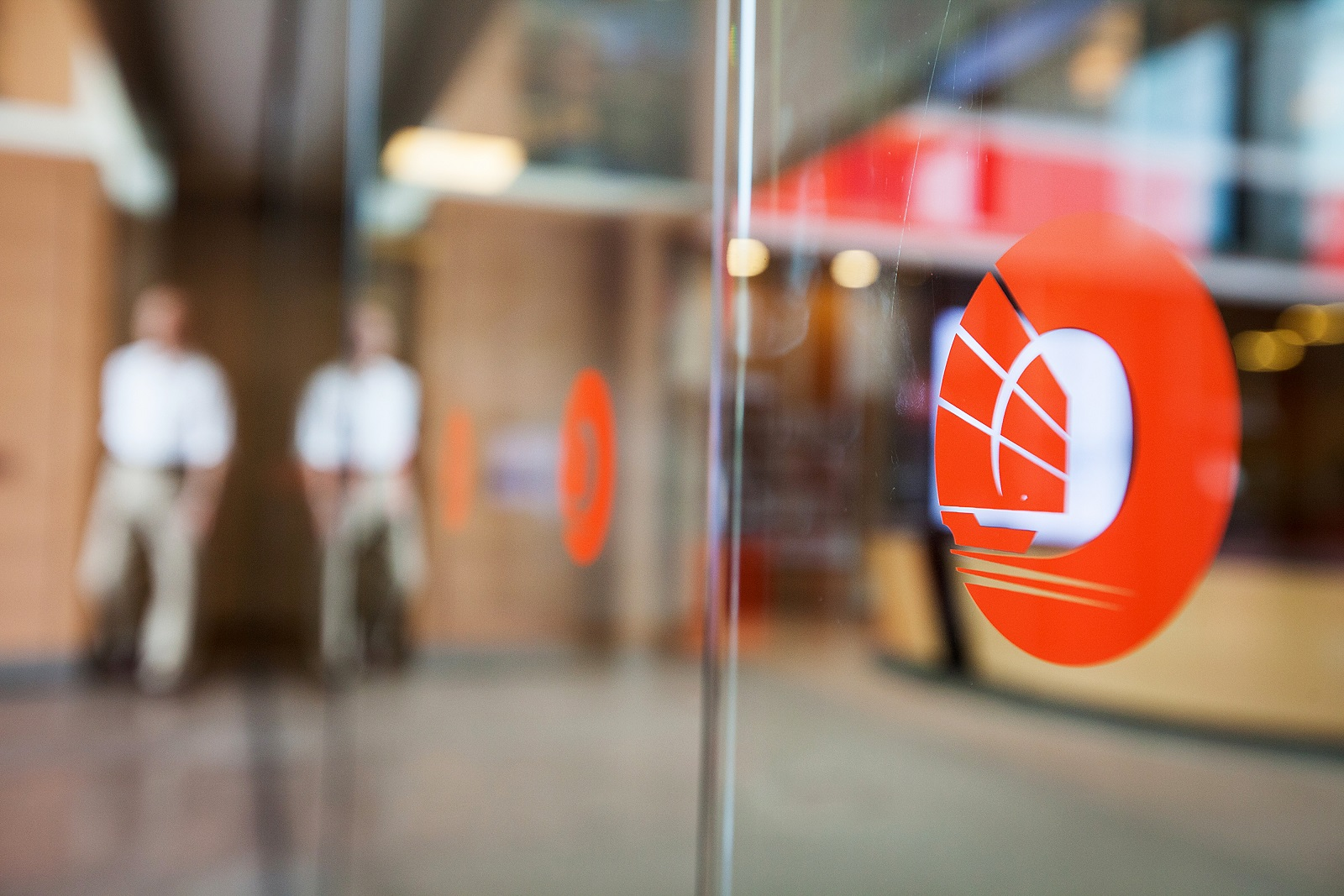 The Oversea-Chinese Banking Corp. logo is displayed on a window at the company's branch in OCBC Center in Singapore, on Friday, Aug. 22, 2014. Oversea-Chinese Banking Corp. is in talks to sell its stake in United Engineers Ltd., a Singapore property and construction company, to Thai billionaire Charoen Sirivadhanabhakdi, people familiar with the matter said. Selling the stake would help OCBC bolster capital after its $5 billion takeover of Hong Kong's Wing Hang Bank Ltd. this year. Photographer: Nicky Loh/Bloomberg