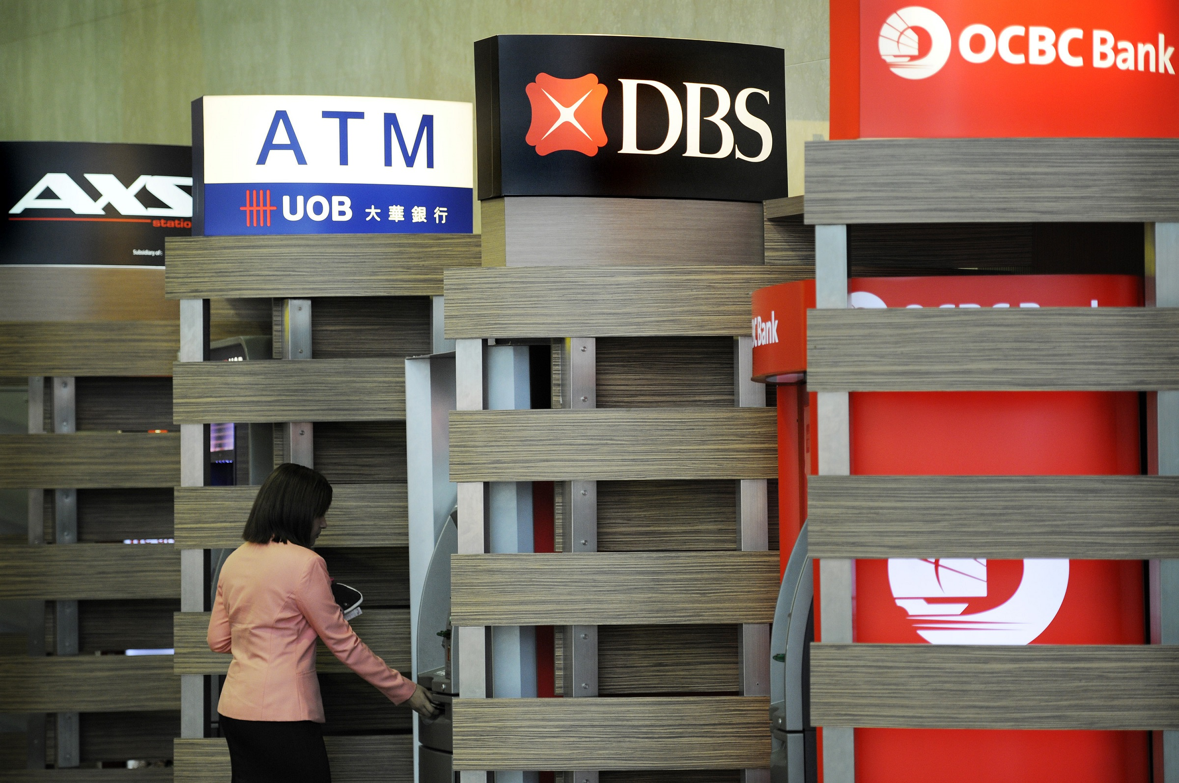 A customer uses a DBS Group Holdings Ltd. automated teller machine (ATM) while other banks booths stand at Changi Airport in Singapore, on Thursday, July 28, 2011. DBS Group Holdings Ltd., Southeast Asia's largest bank, posted second-quarter earnings that missed analysts' estimates as trading income fell 47 percent and loan profitability shrank.  during a results briefing in Singapore, on Thursday, July 28, 2011. Photographer: Munshi Ahmed/Bloomberg