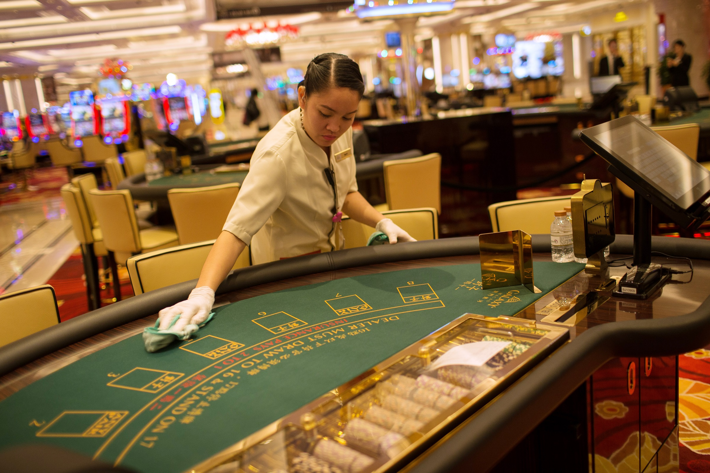 An employee cleans a blackjack table inside the Galaxy Macau Phase 2 casino, developed by Galaxy Entertainment Group Ltd., ahead of its opening in Macau, China, on Wednesday, May 27, 2015. Galaxy is opening Macau's first projects in three years with a concert from Chinese singer Alan Tam, as the casino operator tries to broaden its appeal beyond hardcore gamblers to families and tourists. Photographer: Billy H.C. Kwok/Bloomberg