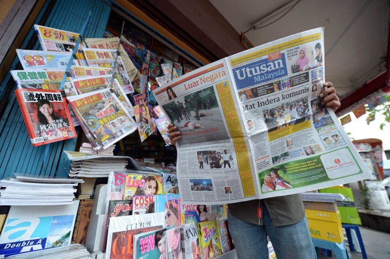 A Malaysian man reads a newspaper outside a shop in downtown Kuala Lumpur on October 10, 2012.  A landmark Malaysian court ruling that upheld an independent news portal's right to publish a newspaper places a spotlight on Prime Minister Najib Razak's pledge to loosen controls on the press.     AFP PHOTO / MOHD RASFAN