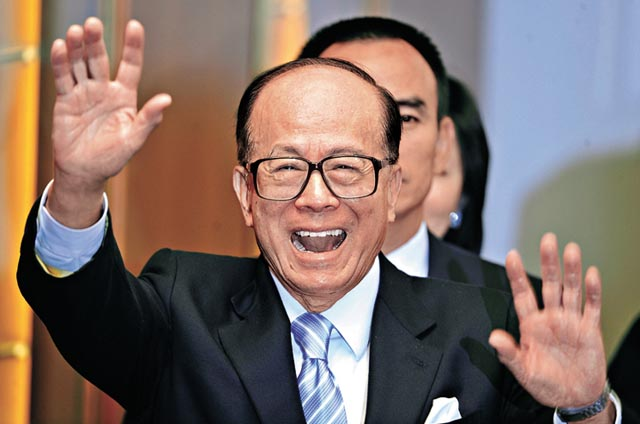 Hong Kong tycoon Li Ka-shing who heads Hutchison Whampoa, waves as he leaves a press conference that announced the company's profits for 2008, in Hong Kong on March 26, 2009. Hong Kong port-to-telecoms conglomerate Hutchison Whampoa said its net profit for 2008 fell 42 percent, as one-off disposal gains had strongly boosted its earnings the previous year. Hutchison, said its net profit for 2008 stood at 17.66 billion Hong Kong dollars (2.3 billion USD), down from 30.60 billion dollars in 2007, total revenue for the firm which has holdings in ports, retail, property, energy, infrastructure and telecoms across the world rose 13 percent in 2008 to 348.37 billion USD.  AFP PHOTO / Antony DICKSON