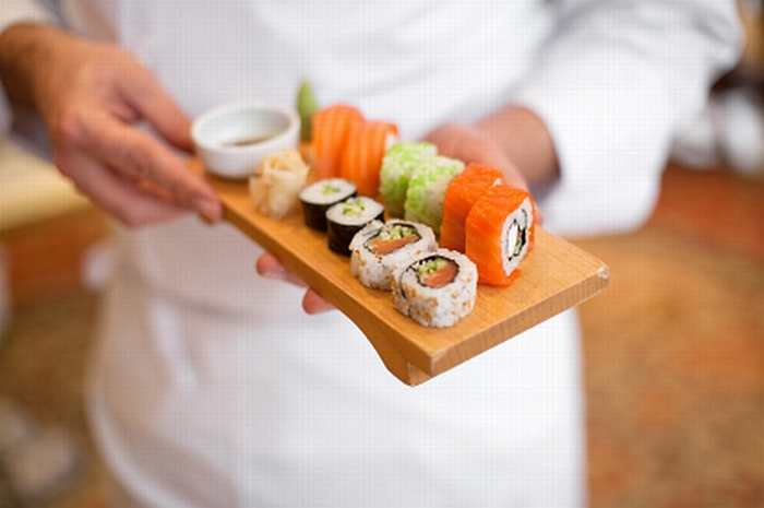 sushi chef holding sushi plate. (shallow depth of field)